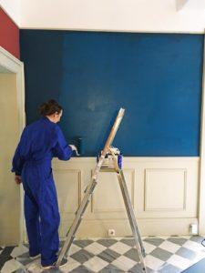 Juliette Percheron en train de peindre le salon de la Maison Arriù